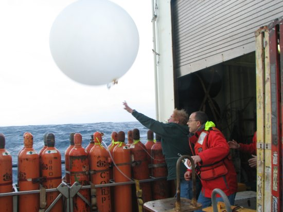 Lou Verstraete and Gary Granger launch a radiosonde balloon in rough conditions during the CLIMODE cruise of the R/V Knorr on the North Atlantic ocean.